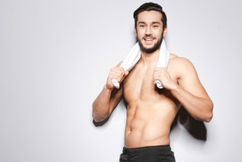 Handsome young man with towel on shoulders looking at camera and smiling while standing against grey background