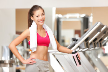 Portrait of fit workout girl with towel standing by treadmills in fitness club